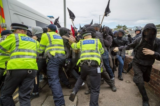 Antifascists break a police cordon.